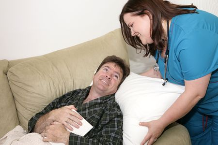 A home health nurse fluffing the pillow of a sick man.  Focus on mans grateful face. photo