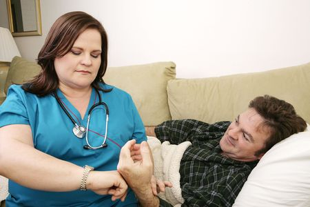 A home health nurse taking the patients pulse.   Stock Photo