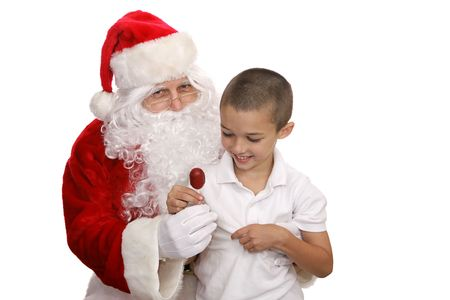 Adorable little boy sitting on Santas lap and getting a lolipop.  Isolated on white.   photo