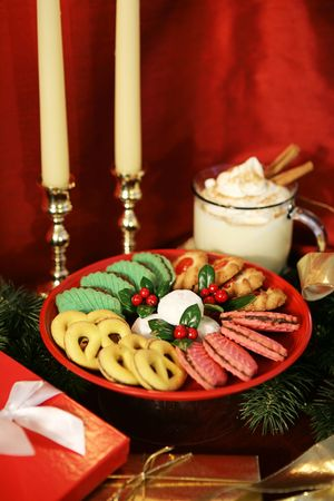 A tray of colorful Christmas cookies garnished with holly, along with eggnog, gifts & candles on a red silk background.  (shallow depth of field with focus on powder sugar cookies in center) Stock Photo - 1914056
