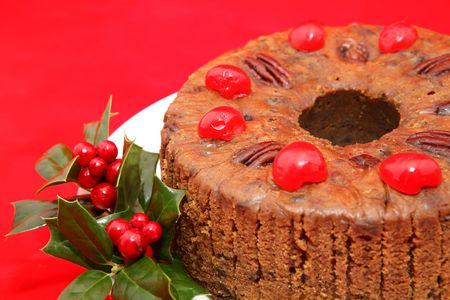 Closeup view of a moist, delicious holiday fruitcake garnished with holly and photographed against a bright red background.   photo