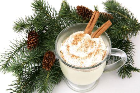 eggnog: Una taza de eggnog adornado con crema batida, nuez moscada y canela palos, ubicado en las ramas de pino. Fondo blanco.