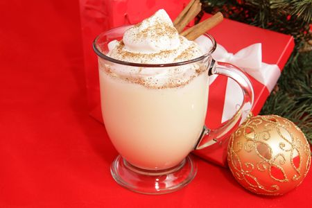A frothy mug of eggnog under the Christmas tree.  Red background with room for text.   photo