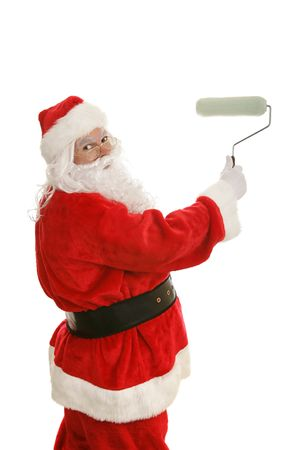 Santa Claus smiling as he rolls paint with a roller.  Isolated on white.