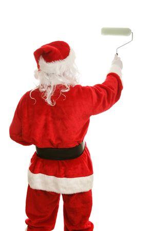 Achteraanzicht van de kerstman schilderij met een verfroller. Geïsoleerd op wit. Stockfoto