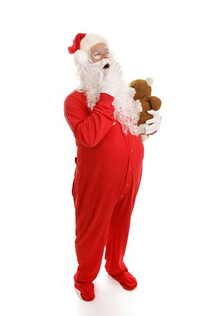 Santa Clause yawning and ready for bed in his footy pajamas with his teddy bear.  Full body on white.   Stock Photo