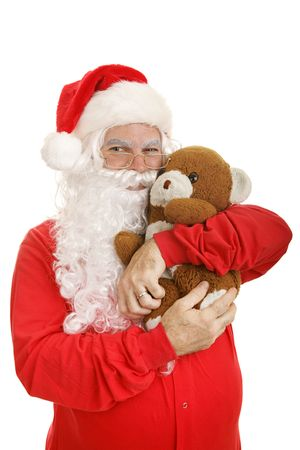 well loved: Santa in his pajamas giving a hug to his well worn and much loved teddy bear.  Isolated on white.