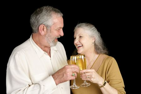 Mature couple laughing and toasting with champagne.  Isolated on black.