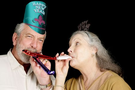 Mature couple in New Years party hats blowing noise-makers.  Isolated on black.   photo