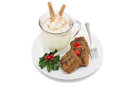 Delicious Christmas fruitcake served with a foamy mug of eggnog.   photo