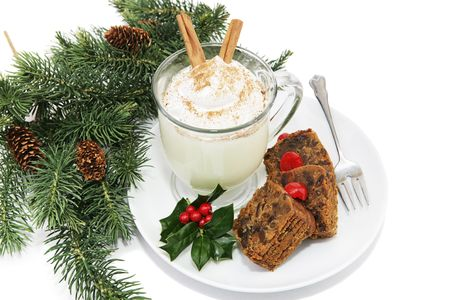 Holiday fruitcake and eggnog on a plate garnished with holly and surrounded by pine branches.  White background.   photo