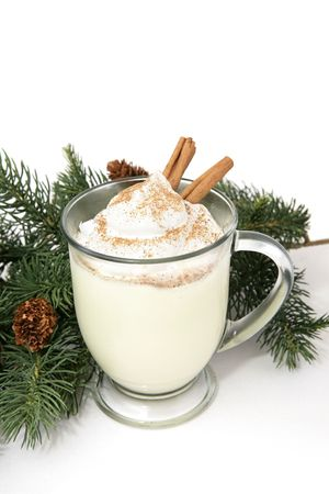 eggnog: Una espesa espumosa taza de eggnog adornado con crema batida, nuez moscada, canela y palos. Fondo blanco con decoraci�n de pinos.