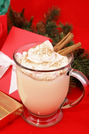Christmas eggnog in a mug with whipped cream, a sprinkling of nutmeg, and cinnamon sticks.  Photographed on a red background surrounded by gifts.