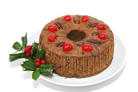 plum pudding: Fruitcake Natale Beautiful guarnita con ciliegie, noci pecan e un rametto di agrifoglio. Isolati su sfondo bianco.