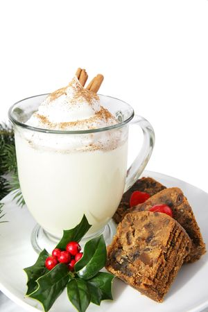 Slices of delicious Christmas cake on a plate with a mug of creamy eggnog.  White background.