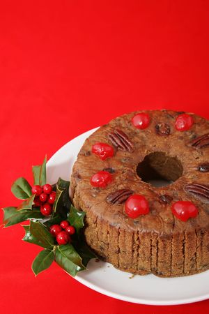 Delicious Christmas fruitcake on a red background with copyspace.