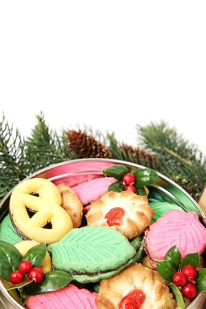 A tin of colorful Christmas cookies surrounded by pine branches.  White background with room for text. photo
