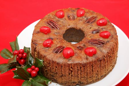 A beautiful holiday fruitcake garnished with holly on a bright red background.