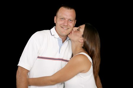 Young pregnant woman kissing her husband on the cheek.  Black background.   photo
