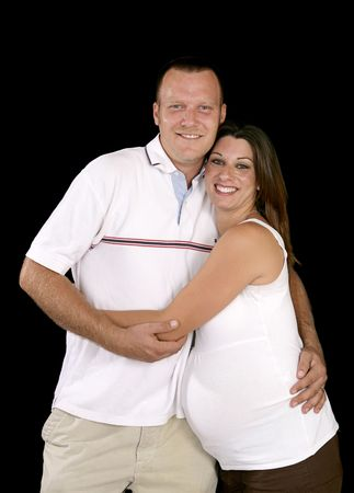Happy, smiling pregnant couple over black background.   photo