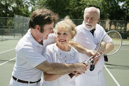 Senior lady taking tennis lessons from a handsome pro while her husband looks on jealously.