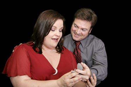 plus sized: Beautiful plus sized model surprised by a marriage proposal.  Black background. Stock Photo