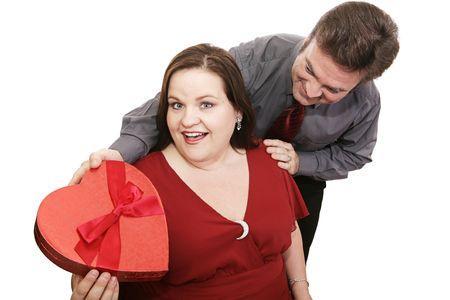 美しいプラスサイズのモデルの彼氏からバレンタインのチョコレートを取得します。白で隔離。 写真素材