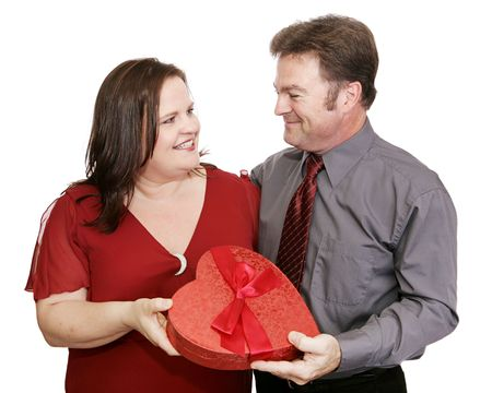 Cute couple exchanging a gift of Valentine candy.  Isolated on white.   photo
