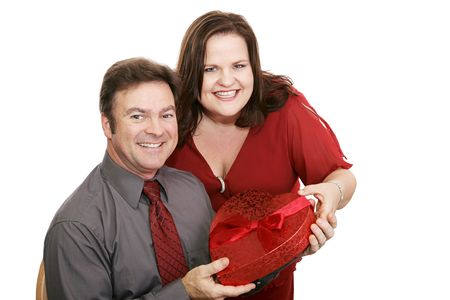 Pretty woman giving her husband a box of valentine chocolates.  Isolated on white. photo