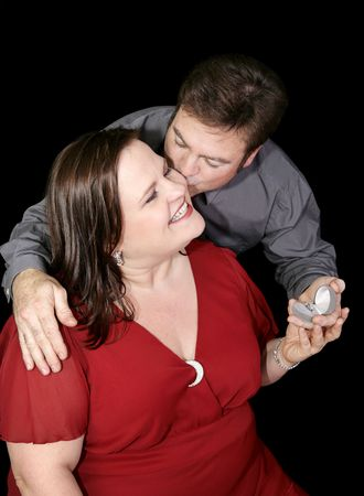 plus sized: Beautiful plus sized model whose boyfriend is proposing to her.  Black background.