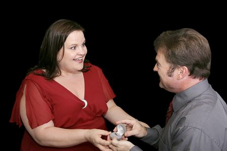 plus sized: Beautiful plus sized model whose boyfriend is on one knee proposing to her.  Black background. Stock Photo