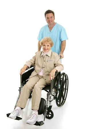 pushed: Pretty senior in wheelchair being pushed by a doctor or male nurse.  Full body isolated. Stock Photo