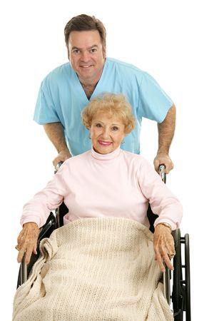 ordelijk: Pretty senior vrouw wordt ontslagen uit het ziekenhuis in een rolstoel met een arts of ordelijk duwen haar. Geïsoleerd op wit.
