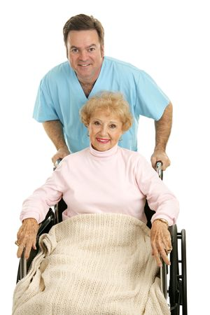 compassionate: Pretty senior woman being discharged from the hospital in a wheelchair with a doctor or orderly pushing her.  Isolated on white.