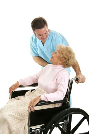 Doctor or male nurse caring for a senior woman in a wheelchair.  Isolated on white.   photo