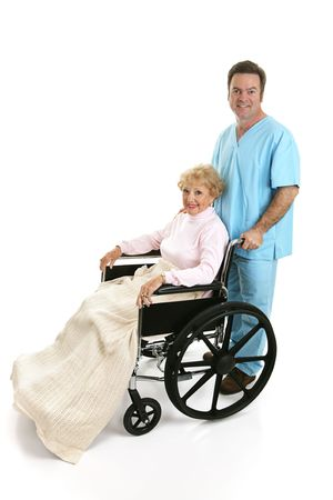 Side view of a disabled senior woman being pushed in her wheelchair by a doctor or male nurse.  Full body isolated on white.   photo