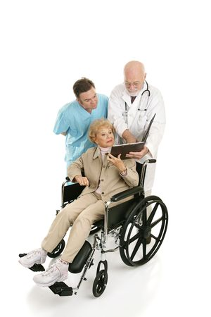 Senior woman in wheelchair discussing her chart with her doctors.  Full body isolated on white photo