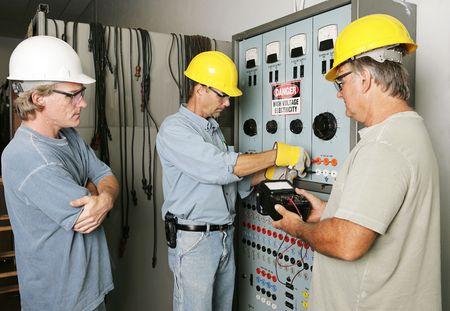 supervisores: Electricistas que trabajan en un centro de distribuci�n industrial de energ�a mientras que relojes del supervisor. Todo el trabajo que es el acordar realizado con c�digo de la industria y est�ndares de seguridad. Foto de archivo