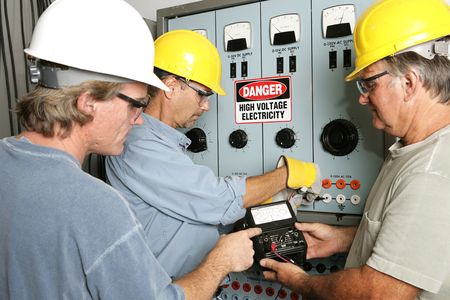 manual job: Group of electricians using an OHM meter to test voltage in an industrial power center.  All work being performed according to industry code and safety standards.  (note to inspector: OHMS on the meter is a unit of measurement not a trademark)