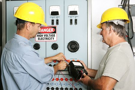 Electricians measuring the voltage output on an industrial power distribution center.  All work is being performed according to industry code and safety standards.
