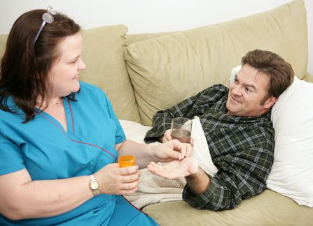 nurturing: Home health care nurse giving a pill to her patient.