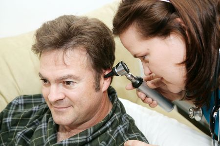 otoscope: Home health nurse using an otoscope to look in her patients ears.