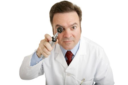 farsighted: Closeup of a doctor peering into an otoscope directly toward the camera.   Stock Photo