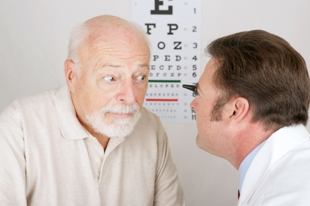 eye care professional: Optician using and ophthalmoscope to look into a patients eyes.