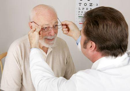 examen de la vista: Optico poner un nuevo par de gafas de lectura sobre un paciente.