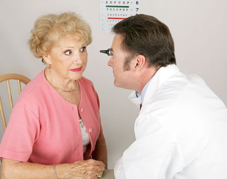 nearsighted: Optician looking into a senior womans eyes during a routine eye exam.   Stock Photo