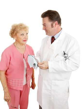 Senior woman talking with her optometrist as he cleans her new glasses.  Isolated on white.   photo