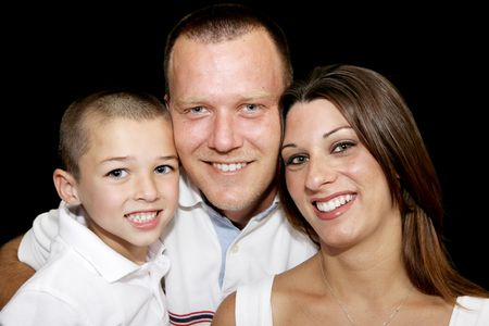 Closeup portrait of a beautiful father, mother, and son on black background.   photo