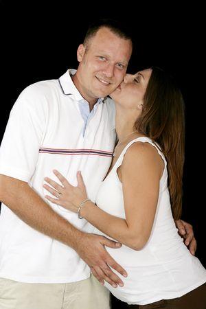 Hermosa mujer embarazada dando a su marido un beso. Fondo negro.  Foto de archivo - 2268860