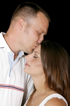 Intimate portrait of a young couple in love.  He is kissing her tenderly on the forehead.